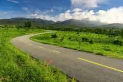 Mooie plattelandsweg op groen gebied onder blauwe hemel Stock Afbeelding