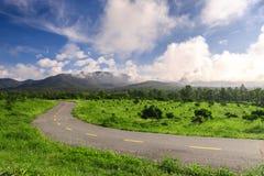 Mooie plattelandsweg op groen gebied onder blauwe hemel Stock Fotografie