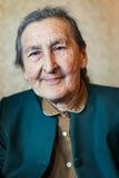 Mooie 80 plus éénjarigen het hogere vrouw stellen voor een portret in haar huis Royalty-vrije Stock Fotografie