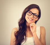 Mooie positieve jonge toevallige vrouw die in glazen en lo denken stock foto