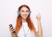Mooie redhairvrouw die in hoofdtelefoons aan muziek luisteren stock foto's