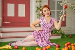Mooie redheaded speld op meisje in sexy roze stipkleding en uitstekende kousen die dichtbij de ingang van haar huis stellen stock afbeelding