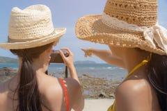 Mooie reizigersvrouwen of mooie vriend die haar vriend mooie foto bij mooi strand in zomer vertellen te nemen royalty-vrije stock afbeelding