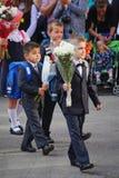 Mooie, rijk en plechtig geklede kinderen met bloemen bij het schoolfestival van kennis Stock Foto's
