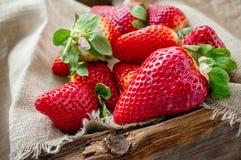 Mooie rijpe aardbeien voor verkoop op een dienblad in houten containers zonder plastiek royalty-vrije stock afbeeldingen
