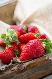 Mooie rijpe aardbeien voor verkoop op een dienblad in houten containers zonder plastiek stock foto