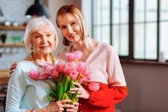 Mooie rijpe dochter die tulpen geven aan gerimpelde grijs-haired moeder royalty-vrije stock afbeelding