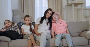 Mooie rijpe moeder met hun twee jonge geitjes één zoon en twee dochters die op TV voor de camera zeer letten stock videobeelden