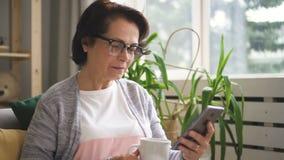 Mooie rijpe vrouw die in glazen koffie drinken stock footage