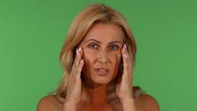 Mooie rijpe vrouw die hoofdpijn hebben stock video