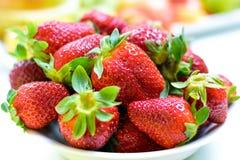 Mooie rode aardbei Hoop van verse aardbeien in ceramische kom op een rustieke witte achtergrond op de lijst stock afbeelding