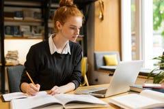 Mooie rode haired tiener die laptop computer met behulp van stock afbeelding