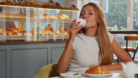 Mooie rode haired vrouw die van koffie en croissant in de ochtend genieten stock video