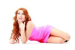 Mooie rode haired vrouw in korte roze kleding stock afbeelding