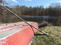 Mooie rode oude rode boot naast vijver Stock Afbeelding