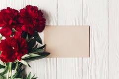 Mooie rode pioenenboeket en ambachtdocument kaart op wit hout Royalty-vrije Stock Afbeelding