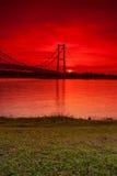 Mooie Rode Zonsondergang dichtbij een Brug Stock Foto