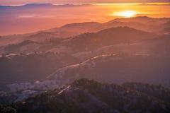 Mooie rollende heuvels gebaad in het zonsonderganglicht; de het plaatsen zon dacht in het water van San Francisco Bay in na royalty-vrije stock fotografie