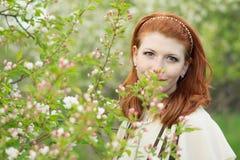 Mooie roodharige meisjesgangen in appelboomgaard Stock Fotografie