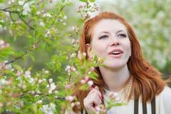 Mooie roodharige meisjesgangen in appelboomgaard Stock Foto's