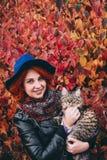 Mooie roodharige vrouw die in blauw hoed en leerjasje met kat in de herfst rood park lopen stock fotografie