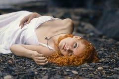 Mooie roodharigevrouw bij het rotsachtige strand Stock Fotografie
