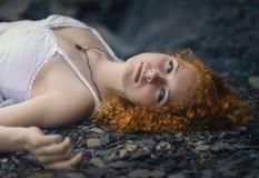 Mooie roodharigevrouw bij het rotsachtige strand stock afbeelding