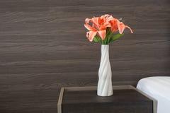 Mooie roze bloem op pot met houten textuurachtergrond in bed Stock Foto