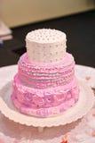 Mooie roze drie-tiered huwelijkscake op lijst Royalty-vrije Stock Foto's