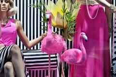 Mooie roze flamingo's met een ledenpop in modieuze kleren achter het winkelvenster royalty-vrije stock fotografie