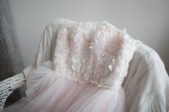 Mooie, roze, lichte kleding van Tulle en kant die op een stoel liggen Het concept van het huwelijk stock afbeelding