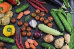 Mooie samenstelling van verschillende die groenten, keurig op een donkere achtergrond wordt opgemaakt Stock Afbeeldingen