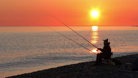 Mooie scène met visserssilhouet met staafzitting op overzees strand stock footage