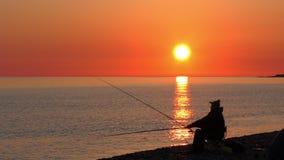 Mooie scène met visserssilhouet met staafzitting op overzees strand stock videobeelden