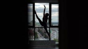 Mooie scène van het uitrekken van sportieve jonge vrouw - meisje die rek van benen doen stock footage