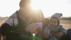 Mooie scène van jonge modieuze familie in casualwear zitting op plaid die en van tijd omhelzen genieten samen, het drinken stock footage
