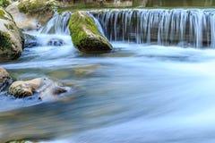 Mooie scène van waterval met steencascade en bemoste rotsen stock foto's