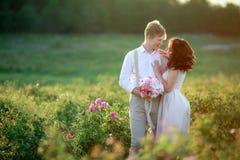Mooie schitterende bruid en modieuze knappe bruidegom, rustiek paar op een roze gebied royalty-vrije stock afbeelding