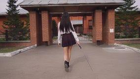 Mooie schoolmeisjegangen trots in langzame motie krassende weg met een katana stock videobeelden