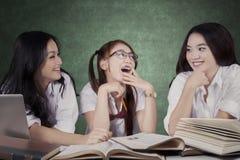 Mooie schoolmeisjes die in de klasse spreken Stock Afbeelding