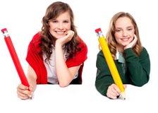 Mooie schoolmeisjes die met groot potlood stellen Royalty-vrije Stock Afbeeldingen