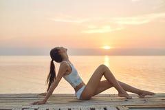 Mooie seksuele vrouw in witte hoed en bikini op een houten pijler tegen het overzees en de zonsondergang Royalty-vrije Stock Afbeeldingen
