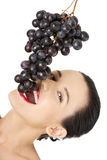 Mooie sensuele brunette die druiven eet Stock Foto's