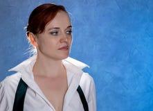 Mooie sensuele jonge vrouw in mannen ` s overhemd en band op een blauwe achtergrond Royalty-vrije Stock Afbeelding