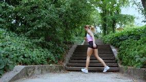 Mooie sexy atletische jonge blonde vrouwenlooppas boven, in het bos, park, in de zomerdag Voert oefeningen aan uit stock video