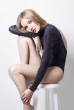 Mooie sexy blonde vrouw Meisje met perfecte lichaamszitting op kruk Mooie lange haar en benen, vlotte schone huid, huidzorg royalty-vrije stock foto's