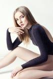Mooie sexy blonde vrouw Meisje met perfecte lichaamszitting op vloer Mooie lange haar en benen, vlotte schone huid, huidzorg royalty-vrije stock fotografie