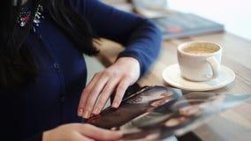 Mooie sexy donkerbruine zitting in een koffie het drinken cappuccino en het bekijken foto's van gedrukt op papier stock footage