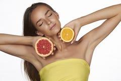 Mooie sexy jonge vrouw die met perfecte gezonde huid en lange bruine de make-up naakte schouders van de haardag oranje citroengra Stock Foto