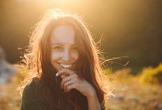 Mooie sexy jonge vrouw die op mooi landschap in zonsondergangtijd glimlachen royalty-vrije stock afbeelding